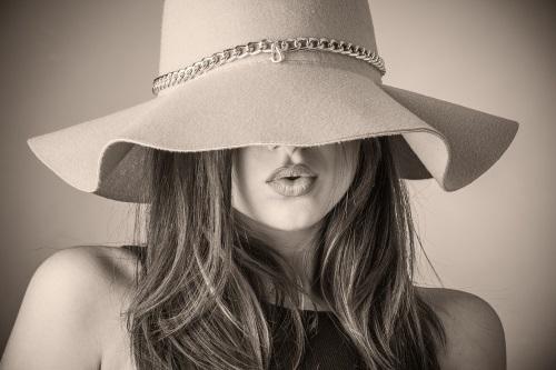 en skönhet med långt hår i hatt